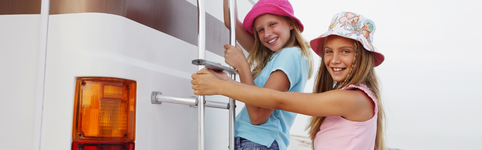 Two girls on a ladder to a trailer
